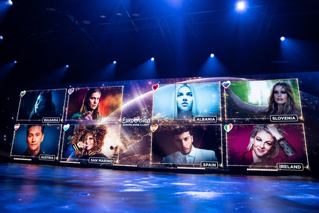 In this Saturday, May 16, 2020 image provided by EBU/NPO/NOS/AVROTROS, artists are shown on screens during the Eurovision's Europe Shine A Light remote television show, in Hilversum, Netherlands. This was no Eurovision Song Contest. Forced by the coronavirus crisis to retreat into a Dutch television studio, Europe's annual musical spectacular that pits countries against one another instead sought to unite them under the shadow of the global pandemic. (Photo by Kris Pouw/EBU/NPO/NOS/AVROTROS via AP Photo)