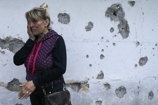 """Tatyana Lystopad, 57, weeps near the wall of her house, which was damaged by shrapnel of artillery shooting in pro-Russian militants controlled village of Staromihailovka, Donetsk area, Ukraine, 19 May 2020. Any direct negotiations with Russian-controlled militants are off the table. """"We only negotiate in the trilateral format: the TCG includes Russia, Ukraine, and the OSCE"""" assures Vice Prime Minister, Minister for Reintegration of Temporarily Occupied Territories, First Deputy Representative of Ukraine to the Trilateral Contact Group for the Donbas settlement, Oleksiy Reznikov on 18 May 2020. (Photo by Dave Mustaine/EPA/EFE)"""
