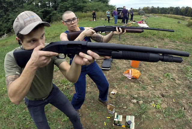 In this October 8, 2017, photo, Jon Falstaff, left, shows Emily Lynch how to properly stand and hold a shotgun during a training session for the Trigger Warning Queer & Trans Gun Club in Victor, N.Y. (Photo by Adrian Kraus/AP Photo)