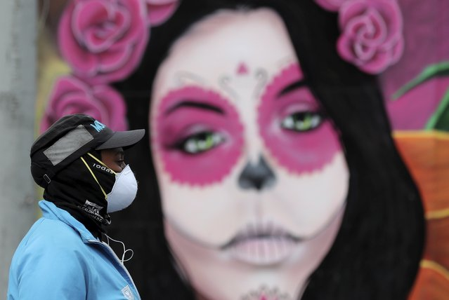 A woman wearing a face mask amid the spread of the new coronavirus walks past a Catrina mural in Bogota, Colombia, Thursday, May 21, 2020. (Photo by Fernando Vergara/AP Photo)