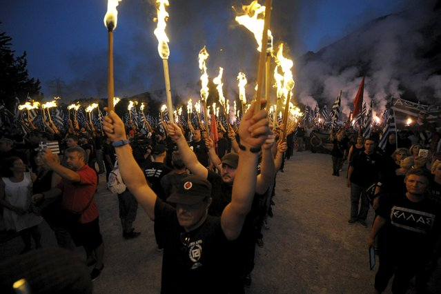 Golden Dawn supporters lift torches as they take part in a ceremony in Thermopylae, outside Athens, Greece, September 5, 2015. Flaming torches raised, far-right Golden Dawn supporters dressed in black chanted the Greek national anthem as darkness fell on Thermopylae, where King Leonidas and 300 Spartans defied a vast Persian army in 480 BC.  (Photo by Alkis Konstantinidis/Reuters)