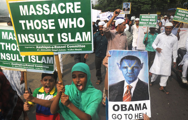 "Indian Muslim children hold anti-US placards as they participate in a protest meeting against the film ""Innocence of Muslims"" in Kolkata on October 5, 2012.  A low-budget, US-produced ""Innocence of Muslims"" movie has incited a wave of bloody anti-US violence in Libya, Egypt, Sudan, Tunisia, Yemen and in several other countries across the Muslim world. (Photo by Dibyangshu Sarkar/AFP/AFP Photo)"