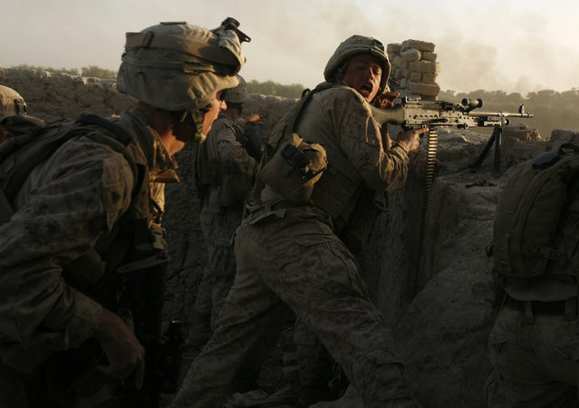 U.S. marines fire during a Taliban ambush as they carry out an operation to clear an area in Helmand province, October 9, 2009. (Photo by Asmaa Waguih/Reuters)