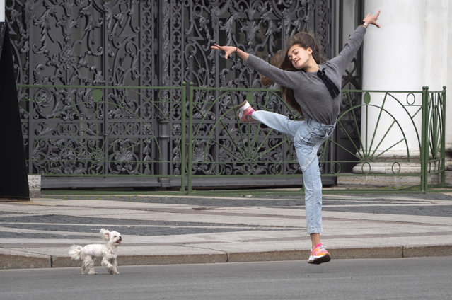 A young woman dances as she walks with her dog at the Palace Square amid the ongoing COVID-19 pandemic in St.Petersburg, Russia, Thursday, May 28, 2020. (Photo by Dmitri Lovetsky/AP Photo)