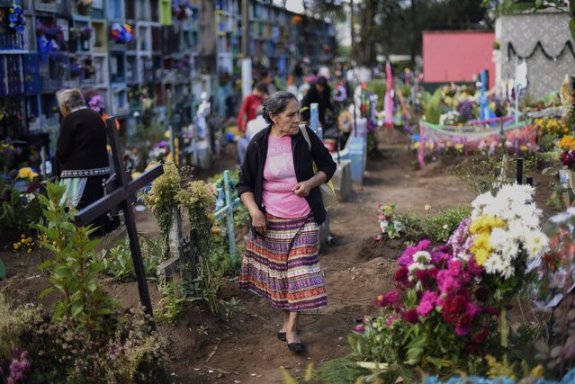 A man adorns a grave at the municipal cemetery of Villa Nueva, 25 km south of Guatemala City, during the celebration of All Saints Day on November 1, 2017. (Photo by Johan Ordonez/AFP Photo)