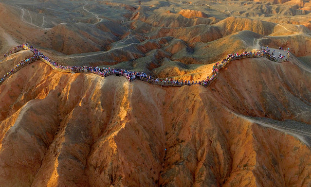 An aerial view shows people visiting an area of Danxia landform in Zhangye, Gansu province, China, August 6, 2016. (Photo by Reuters/Stringer)