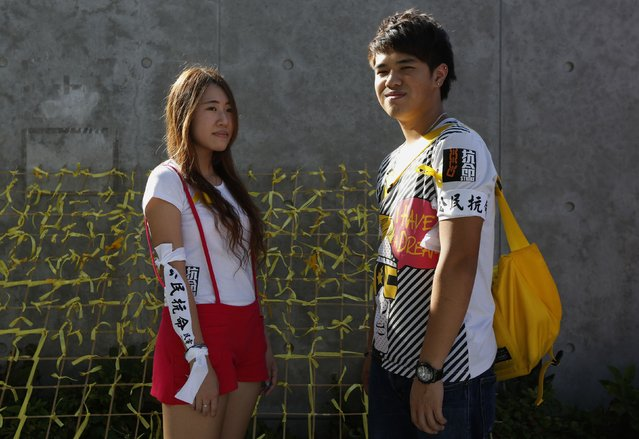 """Genie Mak, 19 (L), and Kitz Yu, 21, both university students, pose for a photograph during a rally ahead of an """"Occupy Central"""" civil disobedience protest in Hong Kong September 26, 2014. Mak said, """"If I don't come out today I may feel regret"""". (Photo by Bobby Yip/Reuters)"""