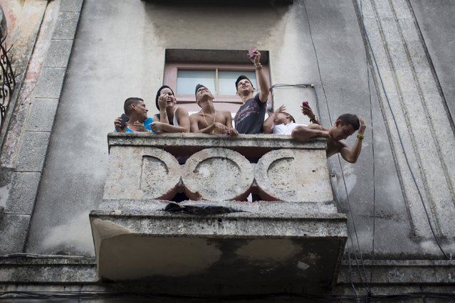 Youths react from a balcony during the annual procession of Our Lady of Charity, the patron saint of Cuba, on the streets of downtown Havana, September 8, 2015. (Photo by Alexandre Meneghini/Reuters)