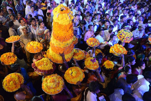 """Indian Hindu women devotees perform rituals with floral displays as they celebrate the """"Bathukamma"""" or """"Life Giver"""" festival in Hyderabad on October 2, 2014.  Women honour the """"Life Giver"""" Bathukamma with flowers that signify both life and eternity in their colours, seeking blessings for prosperity and a good year. This is a synonymous and symbolic festival of the southern state of Telangana and is celebrated during The Navratri (nine nights) Festival. (Photo by Noah Seelam/AFP Photo)"""