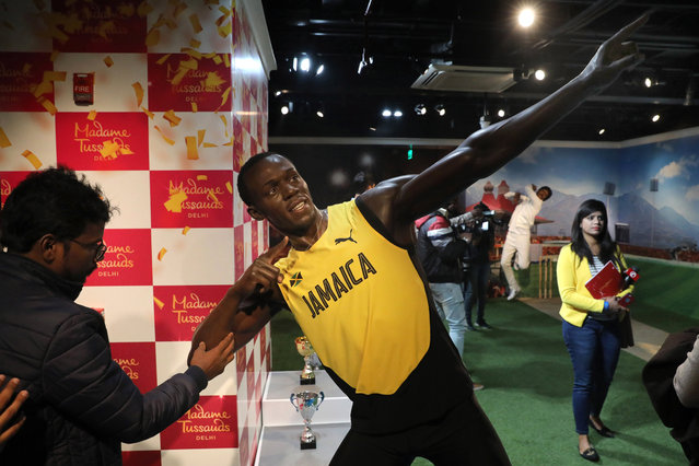 An Indian visitor touches a wax figure of a Jamaican sprinter Usain Bolt at the Madame Tussauds wax museum in New Delhi, India, 30 November 2017. The wax museum will be open for the visitors from 01 December on. Madame Tussauds New Delhi features 50 wax figures of personalities from the fields of sports, music, film, history and politics. (Photo by Rajat Gupta/EPA/EFE)