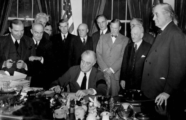 U.S. President Franklin D. Roosevelt signs the declaration of war at the White House in Washington, D.C., December 8, 1941 at 3:08 p.m. EST.  Watching from left to right are, Rep. Sol Bloom, D-N.Y.; Rep. Luther Johnson, D-Texas; Rep. Charles A. Eaton, R-N.J.; Rep. Joseph Martin, R-Mass.; Vice President Henry A. Wallace; House Speaker Sam Rayburn, D-Texas; Rep. John McCormack, D-Mass.; Sen. Charles L. McNary, R-Ore.; Sen. Alben W. Barkley, D-Ky.; Sen. Carter Glass, D-Va.; and Sen. Tom Connally, D-Texas.  (Photo by Associated Press)