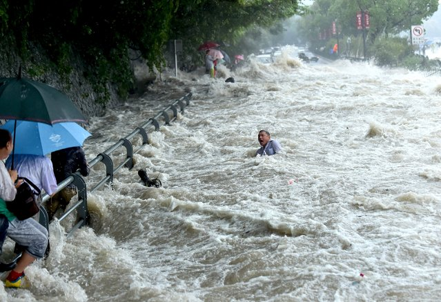 A tourist struggles in the water, before standing up and wading away, after a wave strengthened by the influence of Typhoon Dujuan hit a river bank in Hangzhou, Zhejiang province September 29, 2015. (Photo by Reuters/China Daily)