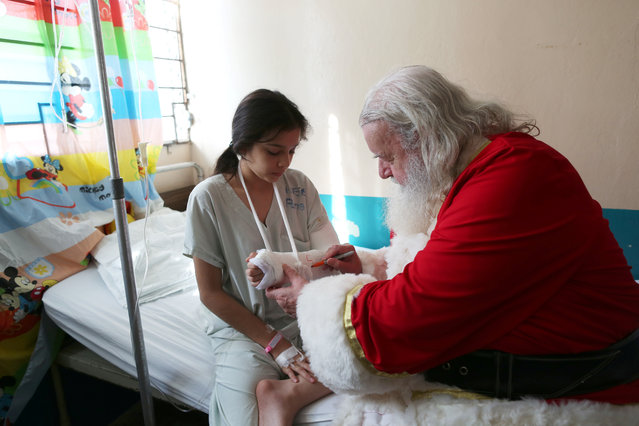 Icelander Einar Sveinsson, dressed as Santa Claus, signs the cast of Ely Daniela Vasquez during a visit to the Benjamin Bloom National Children Hospital in San Salvador, El Salvador on December 18, 2017. (Photo by Jose Cabezas/Reuters)