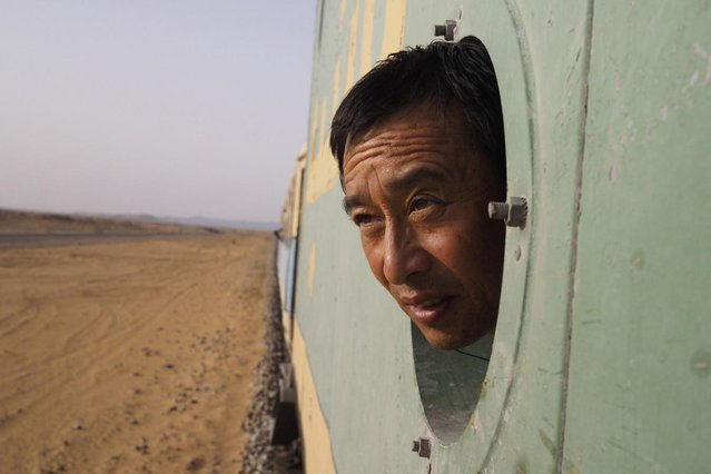 A Chinese businessman looks out the window while on board a SNIM train carrying iron ore and mine workers across the desert outside Zouerate June 24, 2014. (Photo by Joe Penney/Reuters)