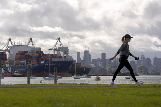 A woman takes a walk in a park during lockdown due to the continuing spread of the coronavirus in Melbourne, Thursday, August 6, 2020. Victoria state, Australia's coronavirus hot spot, announced on Monday that businesses will be closed and scaled down in a bid to curb the spread of the virus. (Photo by Andy Brownbill/AP Photo)