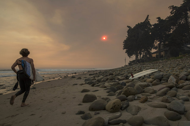 A smoke-filled sky filters sunlight to orange around a surfer as the Thomas Fire continues to grow and threaten communities from Carpinteria to Santa Barbara on December 12, 2017 in Carpinteria, California. The Thomas Fire has spread across 365 miles so far and destroyed about 800 structures since it began on December 5 in Ojai, California. (Photo by David McNew/Getty Images)