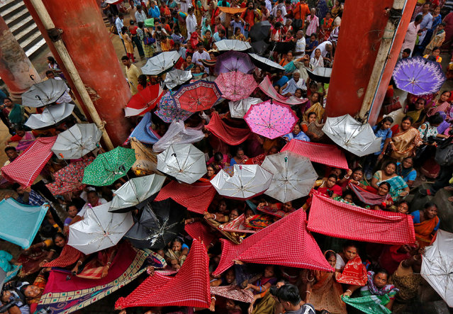Hindu devotees hold up clothes and umbrellas to receive rice as offerings being distributed by a temple authority on the occasion of the Annakut festival in Kolkata, India October 20, 2017. (Photo by Rupak De Chowdhuri/Reuters)