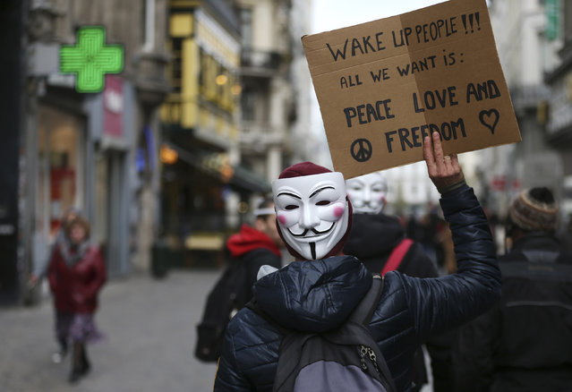A pro-democracy protester wearing a Guy Fawkes mask holds up a sign as he walks in central Brussels November 5, 2014. (Photo by Francois Lenoir/Reuters)