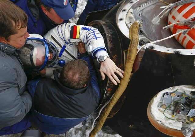 Search and rescue personnel help the International Space Station (ISS) crew member Alexander Gerst of Germany to get out of the Soyuz TMA-13M space capsule after landing in a remote area near the town of Arkalyk in northern Kazakhstan November 10, 2014. (Photo by Shamil Zhumatov/Reuters)
