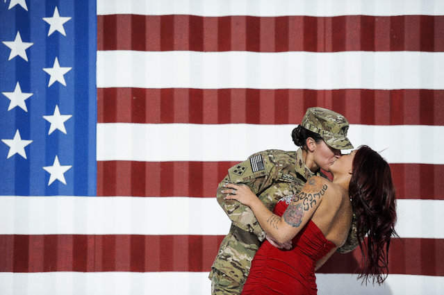 Spc. Sabryna Schlagetter, left, kisses her wife, Cheyenne Schlagetter, after returning home to Fort Carson, Colo., Friday, November 14, 2014, with about 135 members of the 4th Infantry Brigade Combat Team, 4th Infantry Division. Sabryna and Cheyenne married on Valentine's Day this year in New Mexico, nine-months before Sabryna deployed to Afghanistan. (Photo by Michael Ciaglo/AP Photo/The Colorado Springs Gazette)