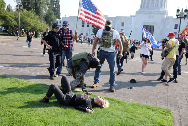Supporters of U.S. President Donald Trump hit a Black Lives Matter activist during a scuffle between the two groups outside the Oregon State Capitol building in Salem, Oregon, U.S. September 7, 2020. (Photo by Carlos Barria/Reuters)