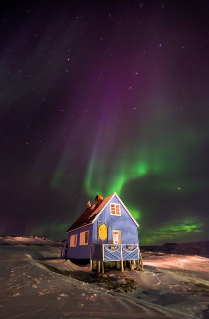 """""""On our second night in the Inuit village of Oqaatsut (formerly Rodebay), West Greenland, we were treated to a display of the dancing green lights of an aurora illuminating this pretty blue house. An unforgettable experience"""". (Photo by Richard Burdon/The Guardian)"""