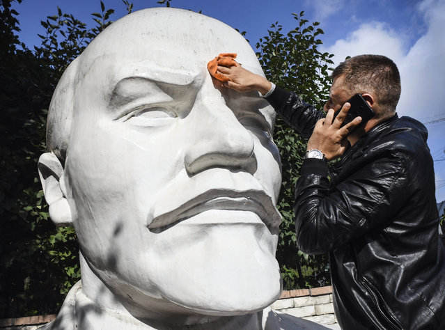 A staff member of a local branch of Russian Communist party washes a huge monument to Vladimir Lenin in front the party's local office in Novosibirsk on September 9, 2020. Communist candidate Renat Suleimanov goes for September 13 regional elections. (Photo by Alexander Nemenov/AFP Photo)