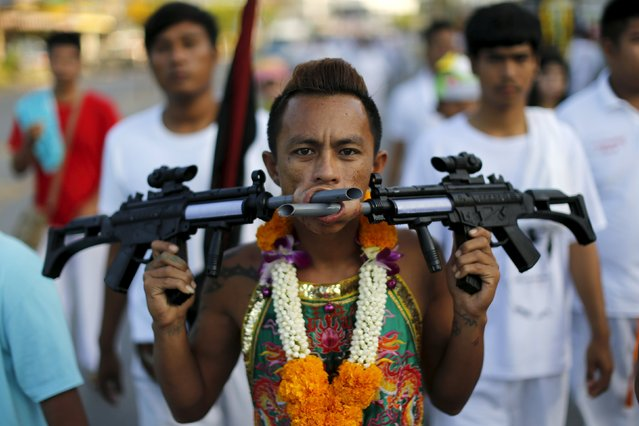 A devotee of the Chinese Ban Tha Rue shrine walks with guns pierced through his cheeks during a procession celebrating the annual vegetarian festival in Phuket, Thailand, October 17, 2015.