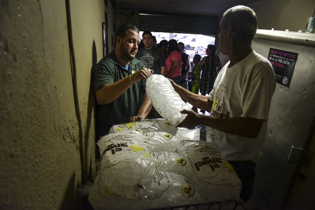 People buy ice during a massive blackout in San Juan, Puerto Rico, Thursday, September 22, 2016. (Photo by Carlos Giusti/AP Photo)
