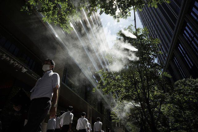 A man wearing a face mask to help curb the spread of the coronavirus walks under a cooling mist spot at a street Friday, September 4, 2020, in Tokyo. The Japanese capital confirmed more than 130 coronavirus cases on Friday. (Photo by ugene Hoshiko/AP Photo)