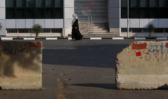 A Palestinian woman walks on a road next to barriers during a lockdown imposed following the discovery of a rise in coronavirus cases in Gaza City, Monday, August 31, 2020. (Photo by Hatem Moussa/AP Photo)