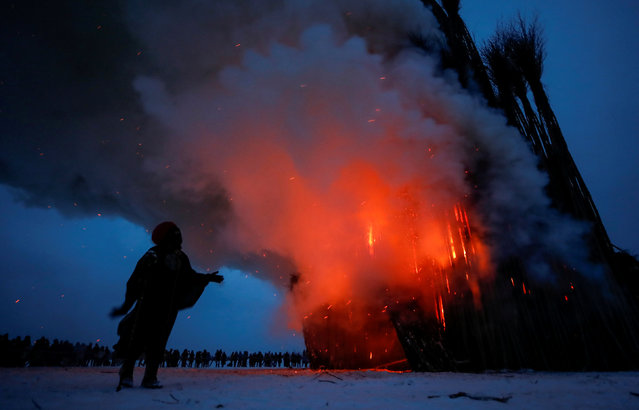 Artist German Vinogradov acts in the performance of the burning of installation, devoted to Maslenitsa, or Pancake Week, a pagan holiday marking the end of winter, in the village of Nikola-Lenivets, Kaluga region, Russia, February 17, 2018. (Photo by Maxim Shemetov/Reuters)