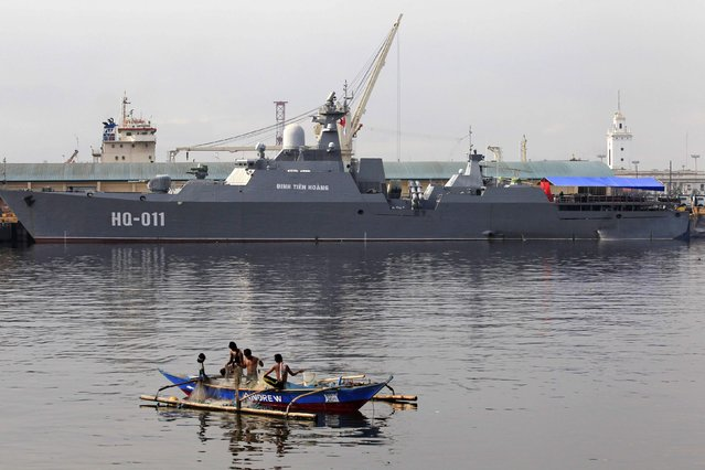 Men, on a small boat, inspect their fishnet in front of one of the two Vietnam Russian-built missile-guided frigates docked at a bay in Manila November 25, 2014. Vietnam on Tuesday showed off its two most powerful warships in the first-ever port call to the Philippines but an official said it was not trying to challenge China's superior naval forces amid tension in the South China Sea. (Photo by Romeo Ranoco/Reuters)