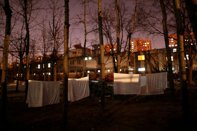 """Laundry hangs on a clothes line in front of the accommodation where some patients and their family members stay while seeking medical treatment in Beijing, China, January 11, 2016. In the shadow of one of China's top cancer hospitals in Beijing, a catacomb-like network of ramshackle brick buildings has become a home-from-home for hundreds of cancer patients and their families waiting for treatment. The cluster of nine buildings, connected by dark, narrow passageways, offers cheap accommodation for patients unable to afford a coveted hospital room, a reflection of the vast inequalities in China's overburdened healthcare system. These """"cancer hotels"""" have sprung up near hospitals around the country to house some of the more than three million people diagnosed with cancer in China every year. (Photo by Kim Kyung-Hoon/Reuters)"""