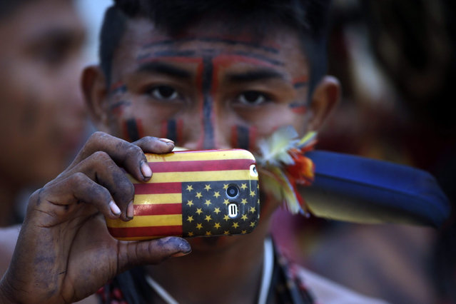 A Brazilian indigenous man takes pictures with his mobile phone during the third day of the World Indigenous Games, in Palmas, Brazil, 25 October 2015. The multisport event, with over 2,000 participating indigenous athletes from 30 countries from all over world, runs until 01 November. (Photo by Fernando Bizerra Jr./EPA)