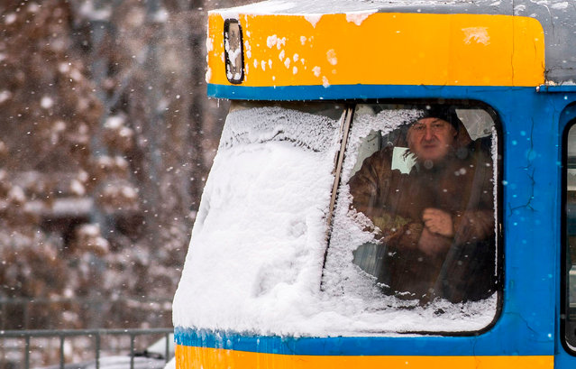 A man looks out from a tram during a heavy snowfall in Sofia on February 26, 2018. A wave of Siberian cold on February 26 fell on the European continent where it had already made the day at least three deaths – one in France and two in Poland. (Photo by Nikolay Doychinov/AFP Photo)