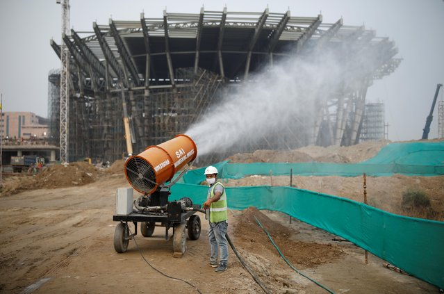 A worker operates an anti-smog gun at a construction site in New Delhi, India, October 14, 2020. (Photo by Adnan Abidi/Reuters)