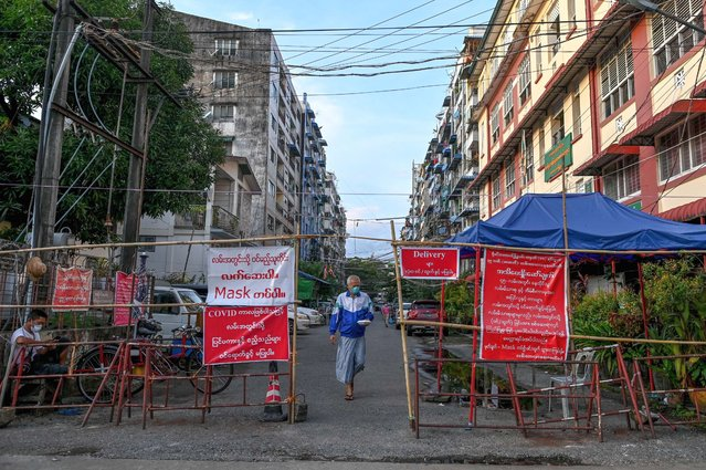 A man walks past a barrier blocking access to minor roads next to a sign recommending to residents to stay at home in Yangon on September 26, 2020, as new restrictions have been introduced to try to halt a surge in Covid-19 coronavirus cases. (Photo by Ye Aung Thu/AFP Photo)