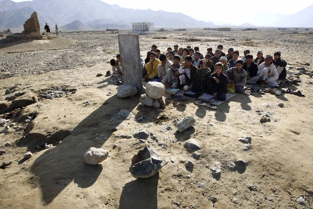 Afghan boys sit on the ground outdoors for their lesson, near Khas Kunar refugee camp, Kunar Province, eastern Afghanistan February 18, 2009. (Photo by Oleg Popov/Reuters)