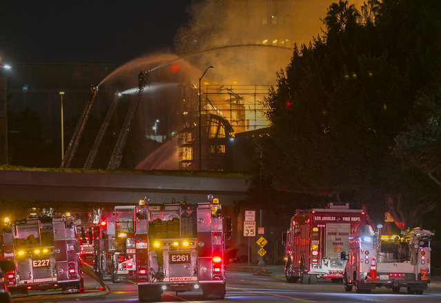 Los Angeles County firefighters battle a fire at an apartment building under construction next to the Harbor CA-110 Freeway in Los Angeles, early Monday, December 8, 2014. (Photo by Damian Dovarganes/AP Photo)