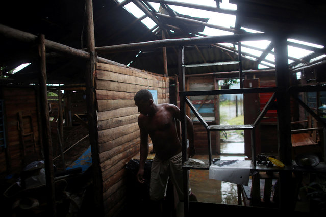 Farmer Edis Gonzalez, 41, walks inside his damaged home after the passage of Hurricane Matthew in Carbonera, Cuba, October 5, 2016. (Photo by Alexandre Meneghini/Reuters)