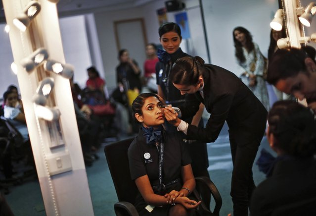 An instructor applies make-up foundation on the face of a prospective flight attendant during a training session at Indigo Airlines' Ifly training centre in Gurgaon on the outskirts of New Delhi November 18, 2014. (Photo by Adnan Abidi/Reuters)