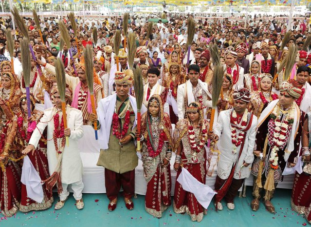 Newly-married Hindu couples hold brooms as they pledge to clean their houses, after taking their wedding wows during a mass marriage ceremony in the western Indian city of Ahmedabad December 6, 2014. A total of 31 Hindu couples from various parts of Ahmedabad took wedding vows during the mass marriage ceremony organised by a Hindu temple trust, organisers said. (Photo by Amit Dave/Reuters)