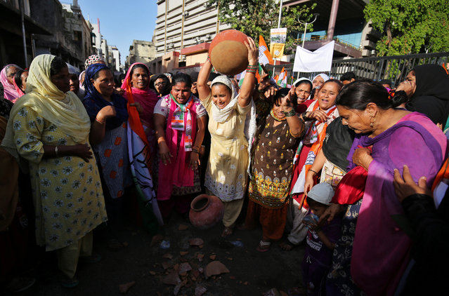 Residents throw earthen pitchers on the ground in protest against the shortage of drinking water, outside the municipal corporation office in Ahmedabad, March 15, 2018. (Photo by Amit Dave/Reuters)