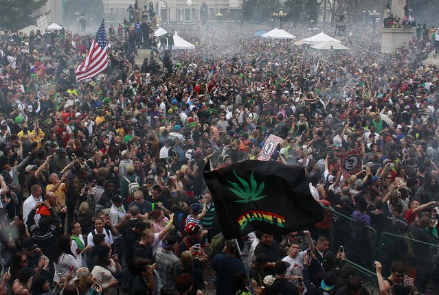 Members of a crowd numbering tens of thousands smoke marijuana simultaneously at 4:20 PM, at the Denver 420 pro-marijuana rally at Civic Center Park in Denver on Saturday, April 20, 2013. (Photo by Brennan Linsley/AP Photo)
