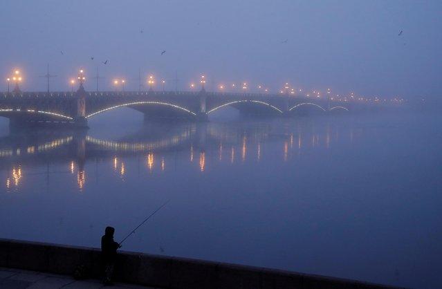 A man fishes near Troitskiy bridge on a foggy morning in Saint Petersburg, Russia on November 1, 2020. (Photo by Anton Vaganov/Reuters)