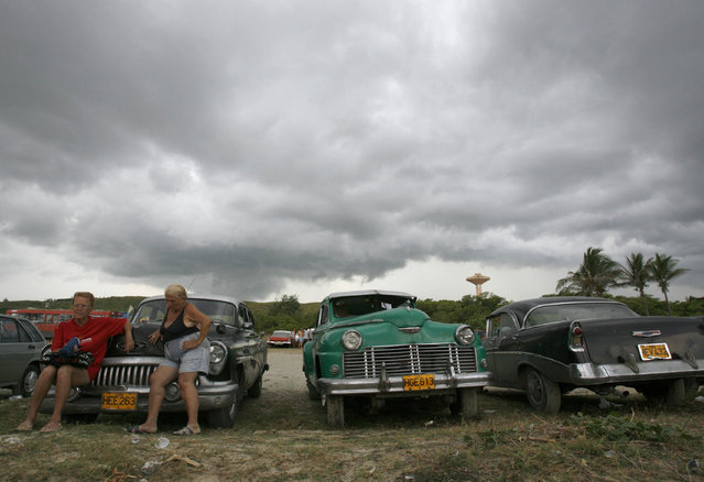 Women rest while sitting on a vintage car in a parking lot at the beach in Guanabo as rain clouds gather, outside Havana, August 12, 2007. (Photo by Claudia Daut/Reuters)