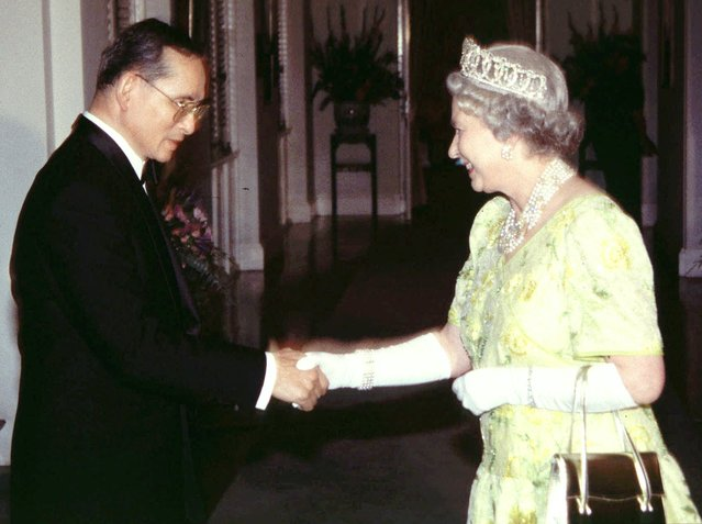 Thailand's King Bhumibol Adulyadej, left, greets Britain's Queen Elizabeth II at a banquet held at the British Embassy in Bangkok Wednesday, October 30, 1996. (Photo by Weerachai Tangmettajittakul/AP Photo/The Nation)