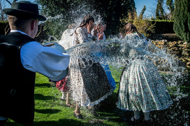 Members of the Mayossa Folk Dance Group pour water on young women in Kiskunmajsa, some 140 kms southeast of Budapest, Hungary, Monday, April 2, 2018. According to a several hundred years old tradition of Hungarian villages young men pour water on young women who in exchange present their sprinklers with beautifully colored eggs on Easter Monday. (Photo by Sandor Ujvari/MTI via AP Photo)