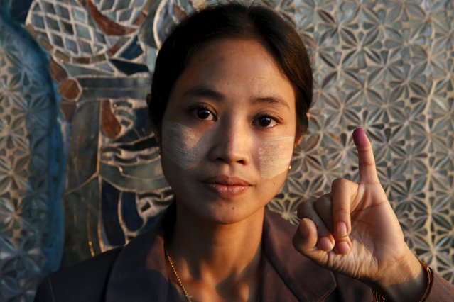 A woman shows her inked finger after voting at a Buddhist prayer hall during the general election in Mandalay, Myanmar, November 8, 2015. (Photo by Olivia Harris/Reuters)